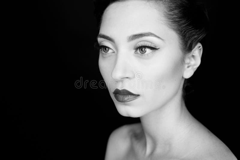 Retrato preto e branco do encanto de uma mulher séria bonita com bordos pretos fotografia de stock royalty free