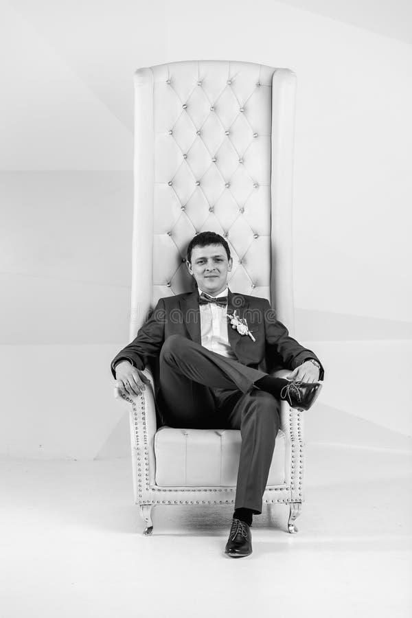 Retrato preto e branco do homem considerável que levanta no estúdio no braço fotos de stock royalty free