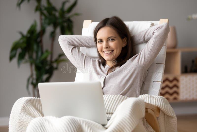 Retrato principal del tiro de la mujer atractiva que usa el ordenador portátil, relajándose en silla fotos de archivo libres de regalías