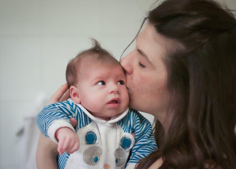 Retrato principal do mum que beija seu bebê recém-nascido fotos de stock