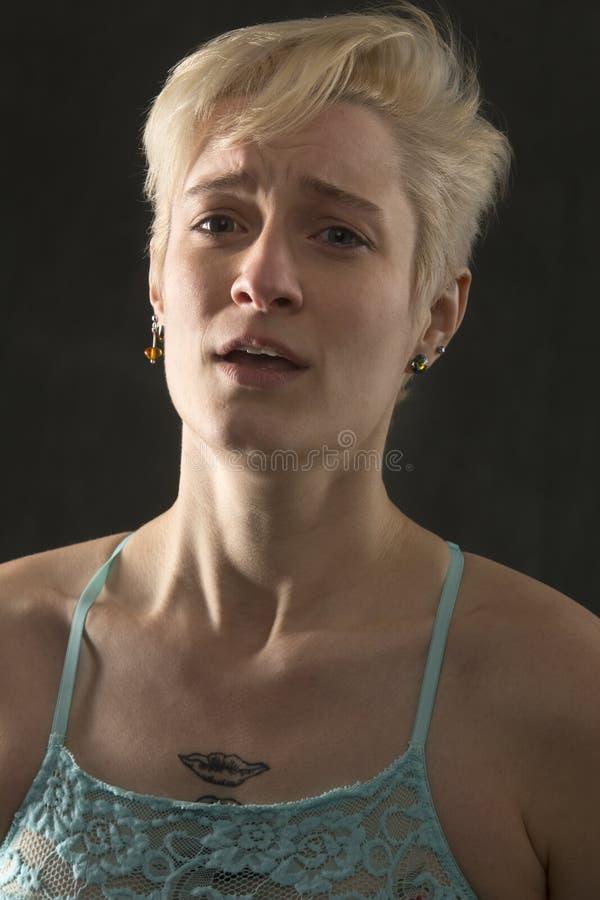 Retrato principal e dos ombros da jovem mulher na grande dor foto de stock