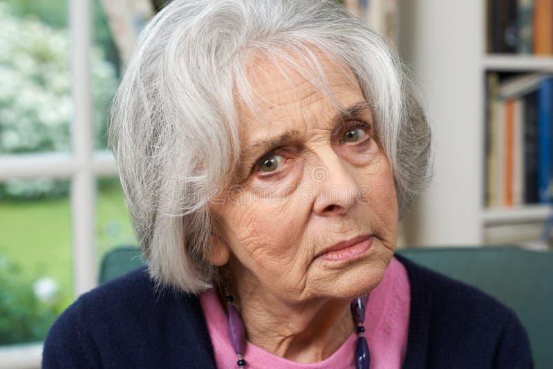 Retrato principal e dos ombros da mulher superior infeliz em casa imagens de stock royalty free