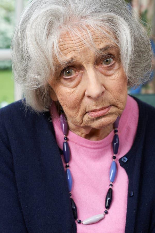 Retrato principal e dos ombros da mulher superior infeliz em casa imagem de stock royalty free
