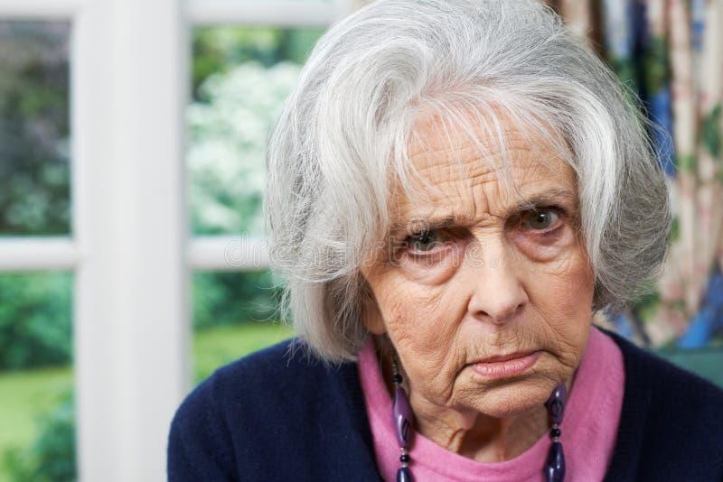 Retrato principal y de los hombros de la mujer mayor enojada en casa fotografía de archivo libre de regalías