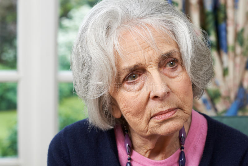 Retrato principal y de los hombros de la mujer mayor pensativa en casa fotos de archivo