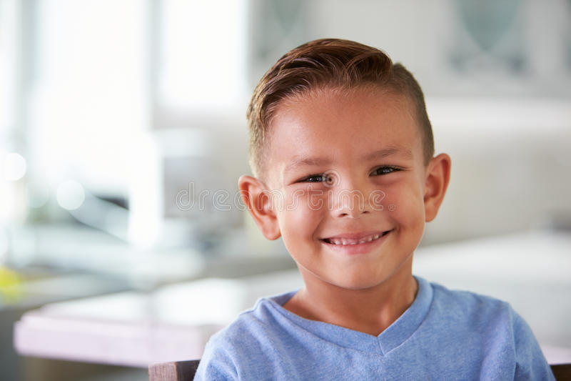 Retrato principal y de los hombros del muchacho hispánico sonriente en casa fotografía de archivo libre de regalías