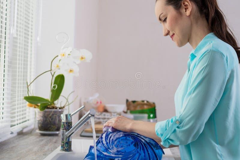 Retrato quadro de uma dona de casa na frente de uma janela na cozinha, lavando um prato azul sob a água corrente fotos de stock