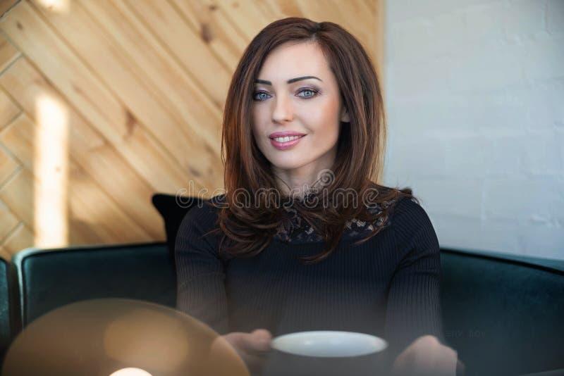 Retrato que encanta a la mujer joven con sonrisa amistosa, caf? sonriente del pelo moreno largo imágenes de archivo libres de regalías