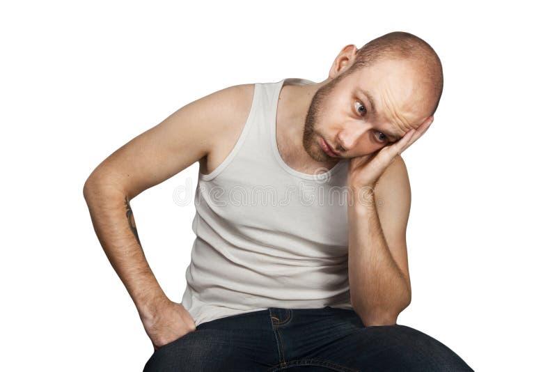 Retrato que un individuo calvo en una camiseta blanca se sienta en una silla y que piensa en problemas con el dinero, soledad, pa fotos de archivo