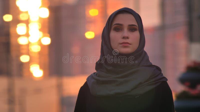 Retrato recto del primer de la hembra bonita joven en el hijab que mira adelante la cámara con la ciudad urbana y que brilla imágenes de archivo libres de regalías