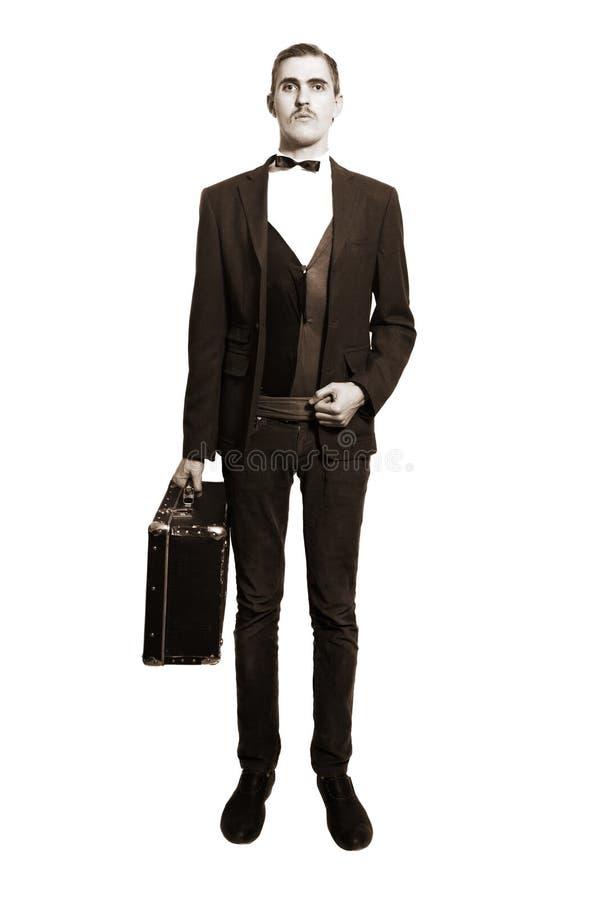 Retrato retro del hombre joven con la maleta aislada imagenes de archivo