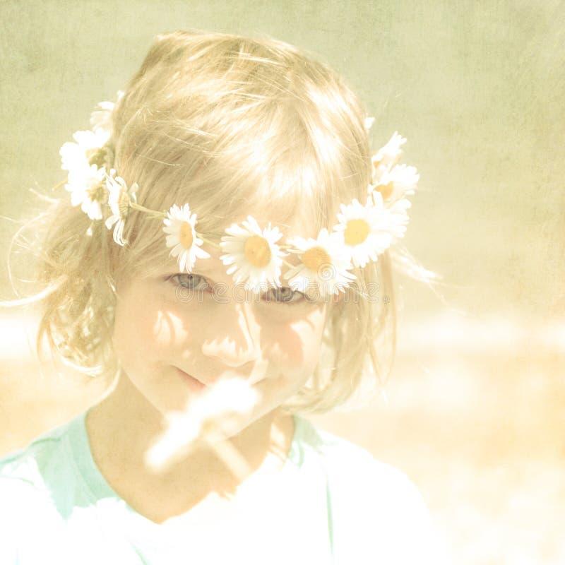 Retrato retro texturizado de la muchacha rubia bastante pequeña con una corona de margaritas imagen de archivo libre de regalías