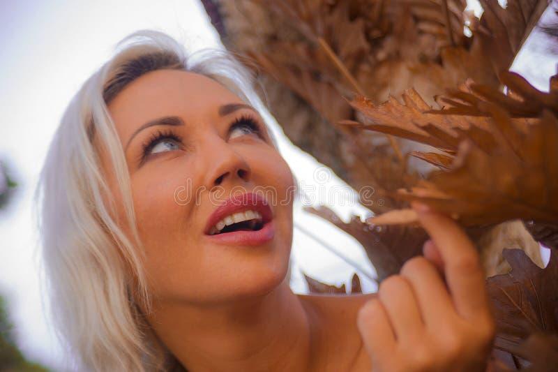 Retrato romántico del aire libre de la hoja rubia atractiva y hermosa joven del árbol de la tenencia de la mujer relajada y de la imagenes de archivo