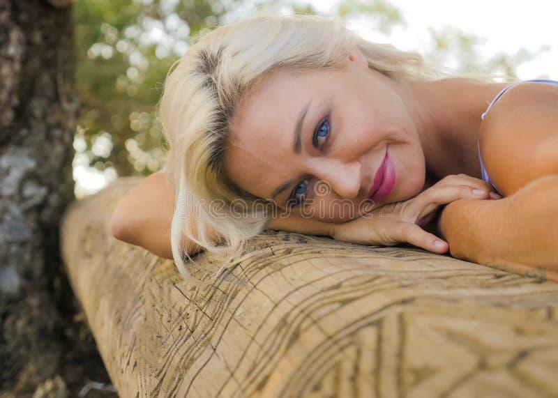 Retrato romántico del aire libre de la mujer rubia atractiva y hermosa joven que se inclina la cara relajada y feliz en tronco de imagen de archivo libre de regalías