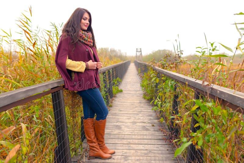 Retrato romântico da mulher do outono que sorri fora no parque Posição bonita da jovem mulher em uma ponte de madeira que apre imagem de stock royalty free