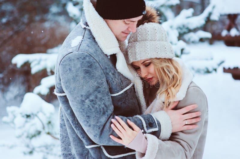 retrato romântico do inverno dos pares que abraçam exterior na caminhada na floresta nevado fotografia de stock royalty free