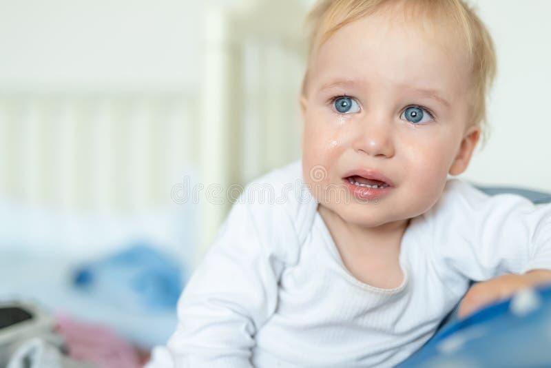 Retrato rubio cauc?sico lindo del ni?o peque?o que llora en casa durante histeria Poco sensaci?n del ni?o triste Peque?o beb? pen imagenes de archivo