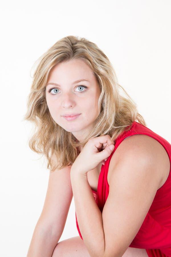 Retrato rubio de la muchacha sonriente joven que se coloca con las manos dobladas imagen de archivo