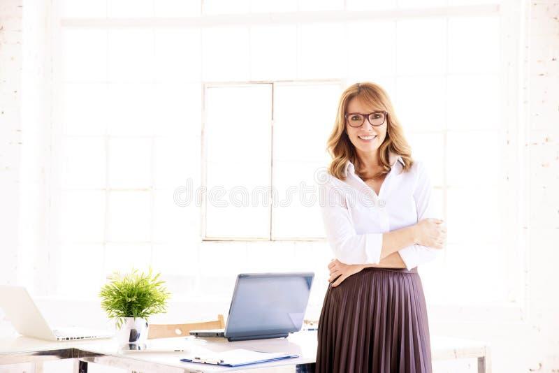 Retrato seguro atrativo da mulher de negócios ao estar no escritório imagem de stock