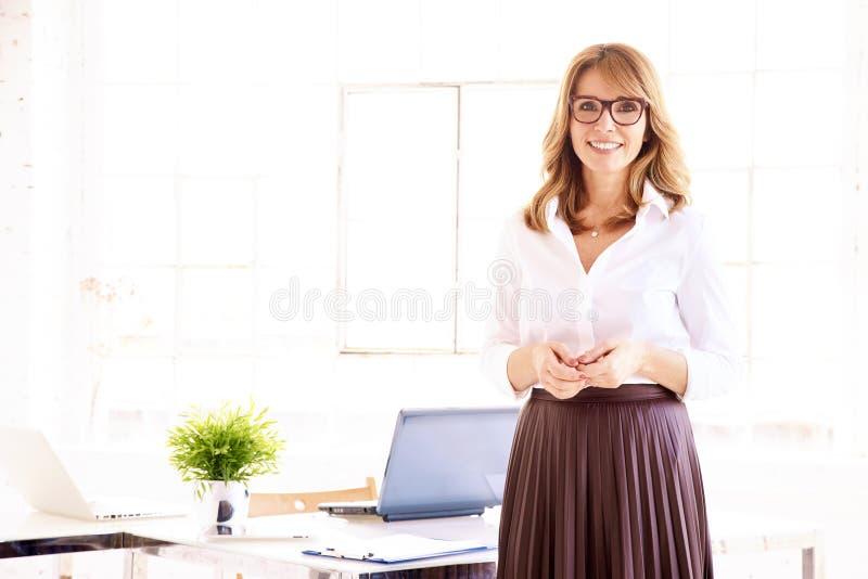 Retrato seguro atrativo da mulher de negócios ao estar no escritório imagens de stock