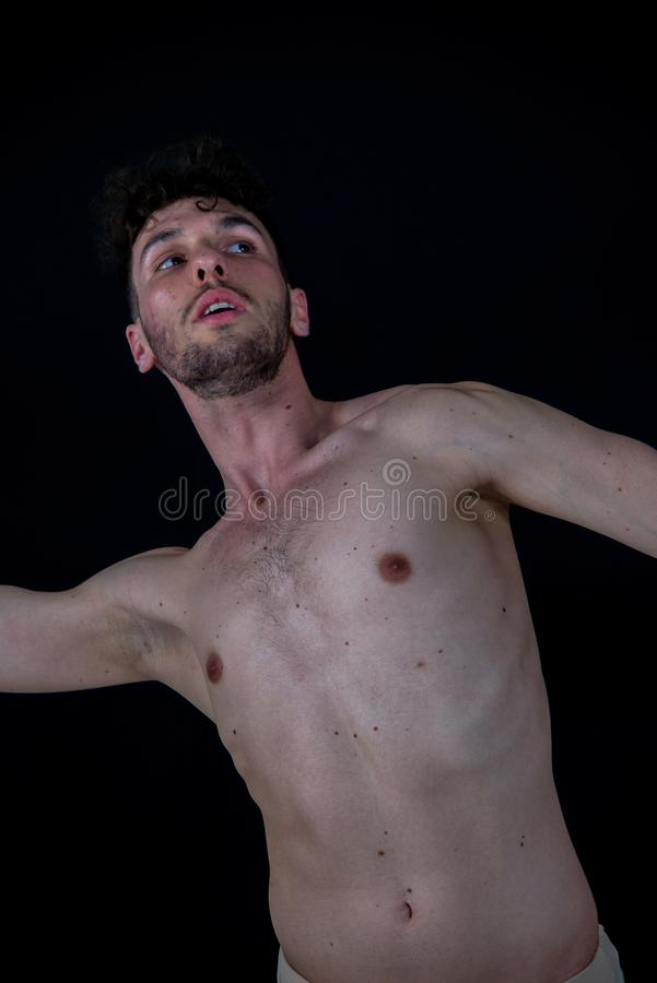 Retrato semidesnudo de un bailar?n de sexo masculino joven, en movimientos referentes al baile con sus manos fotografía de archivo