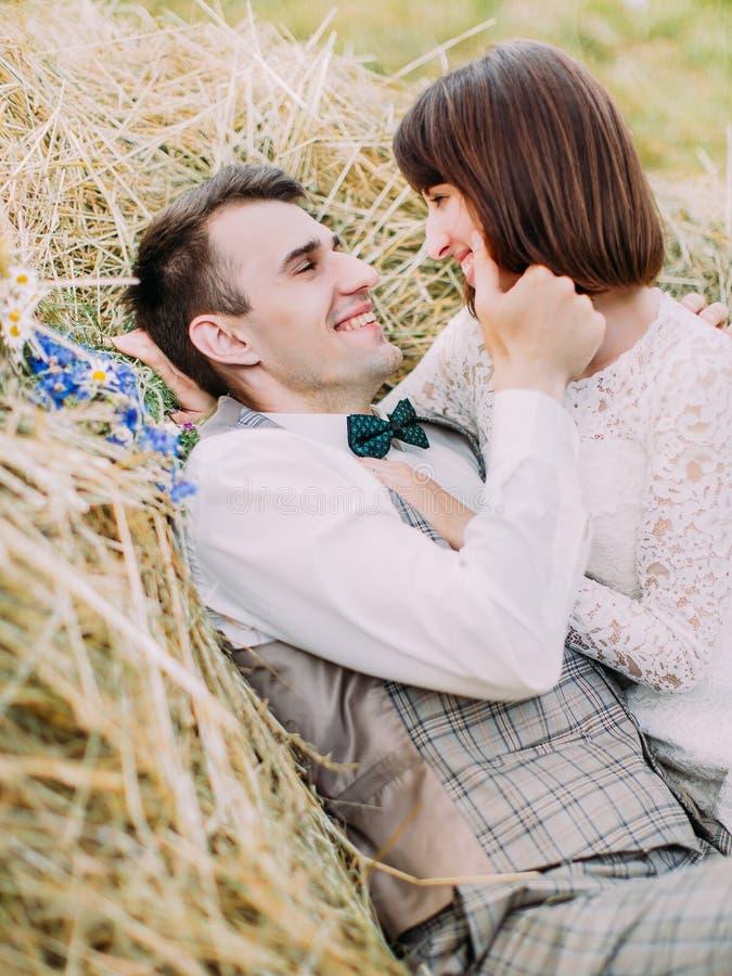 Retrato sensible de los recienes casados sonrientes El novio está frotando ligeramente la mejilla de la novia mientras que miente imagenes de archivo