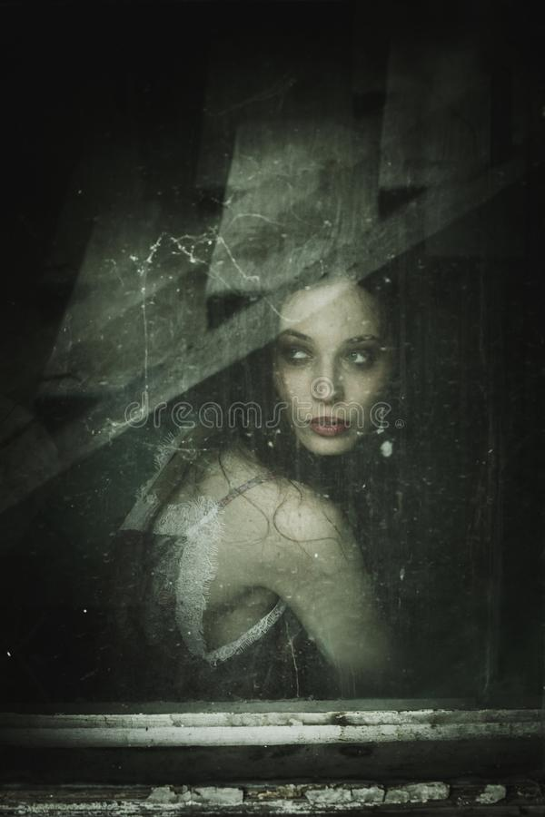 Retrato sensual da jovem mulher atrás da janela suja velha imagens de stock royalty free