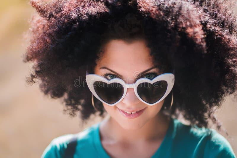 Retrato sensual de la mujer bonita joven con el peinado rizado africano y las gafas de sol en forma de corazón Muchacha hermosa c imagen de archivo