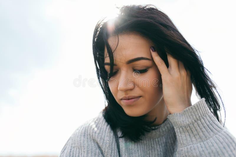 Retrato sensual del viajero caucásico moreno de la mujer joven con el pelo ventoso, soñando contra el cielo de la luz del sol Hem fotografía de archivo