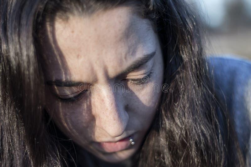 Retrato serio joven de la mujer que considera abajo la oscuridad fotos de archivo