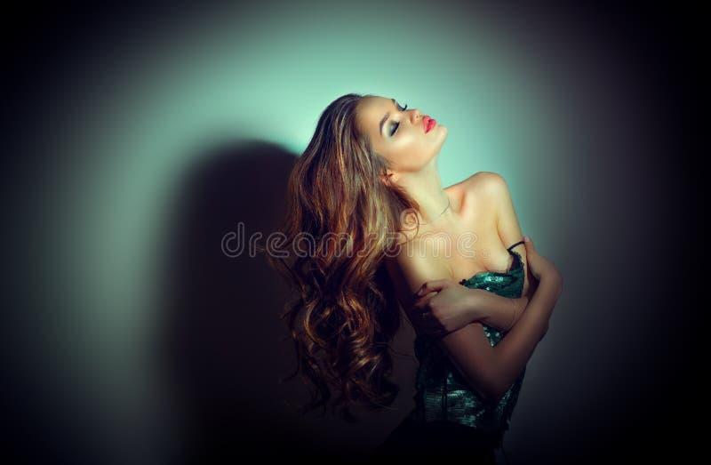 Retrato 'sexy' da mulher nova Menina moreno sedutor que levanta na escuridão Senhora do encanto da beleza com cabelo encaracolado imagens de stock