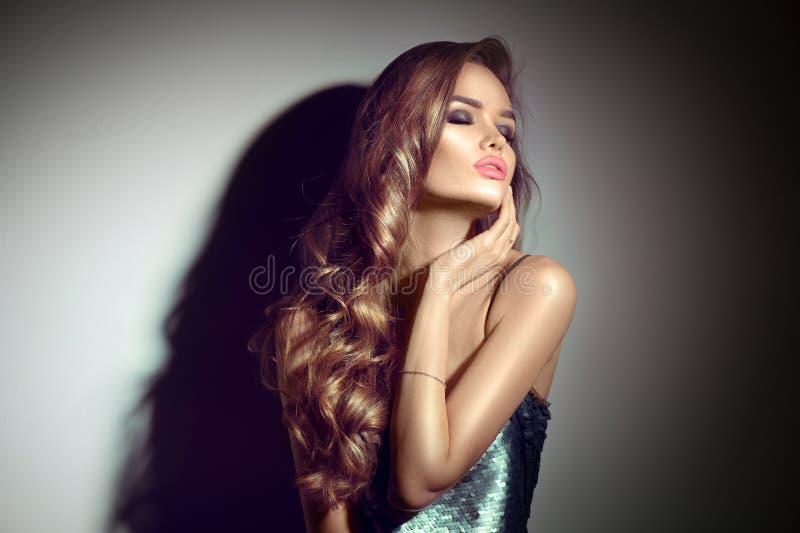 Retrato 'sexy' da mulher nova Menina moreno sedutor que levanta na escuridão Senhora do encanto da beleza com cabelo encaracolado fotografia de stock royalty free