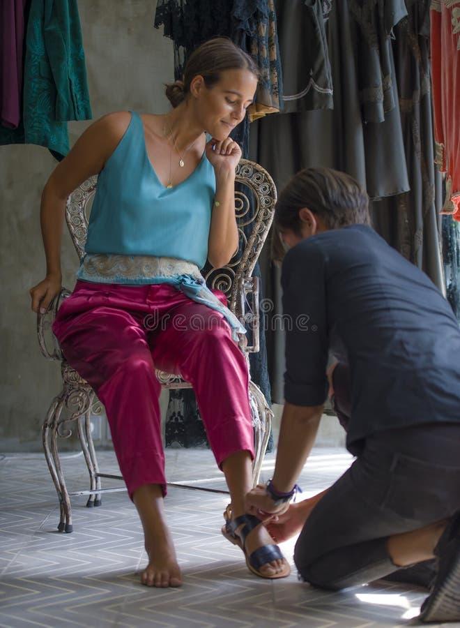 Retrato sincero de la forma de vida de la mujer rubia hermosa y feliz joven que disfruta de hacer compras probando las sandalias  imagen de archivo