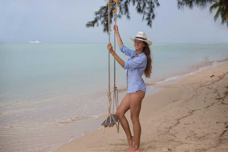 Retrato solar do verão da forma de um modo de vida da mulher à moda nova, sentando-se em um balanço na praia, fashi bonito levand imagens de stock