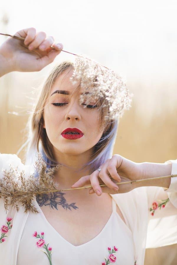 Retrato soleado de una chica joven hermosa en el fondo de un campo de trigo foto de archivo libre de regalías