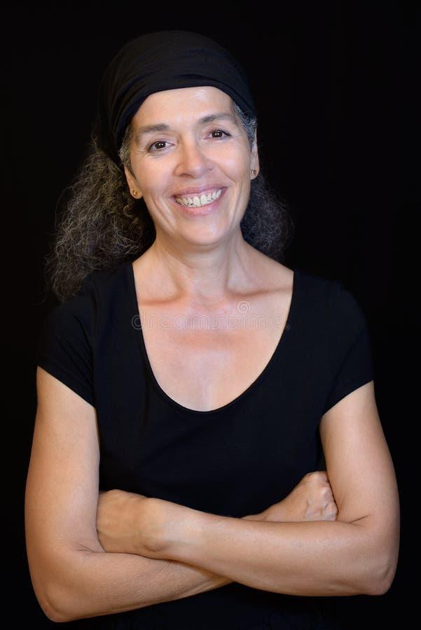 Retrato sonriente de la mujer 50+ que lleva el fondo negro negro imagen de archivo