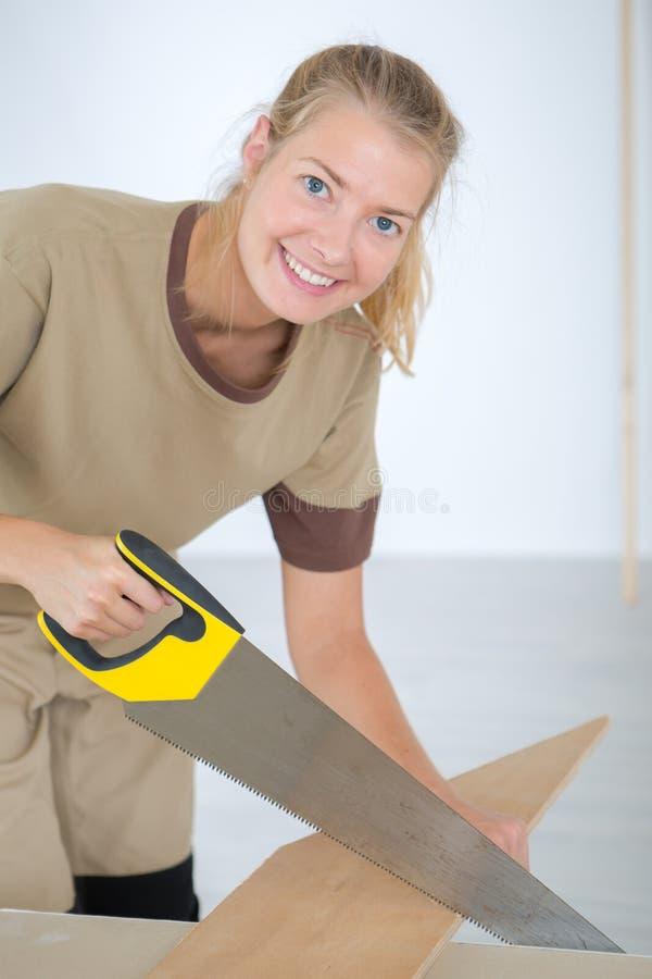 Retrato sonriente de madera del sawing de la mujer imágenes de archivo libres de regalías