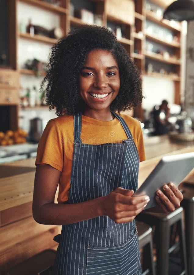 Retrato sonriente de un dueño femenino que sostiene la tableta digital en ella foto de archivo libre de regalías