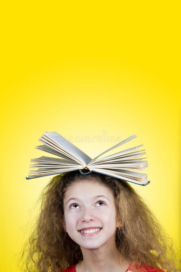 Retrato sonriente de una pequeña colegiala linda que ama aprender ingenio fotos de archivo