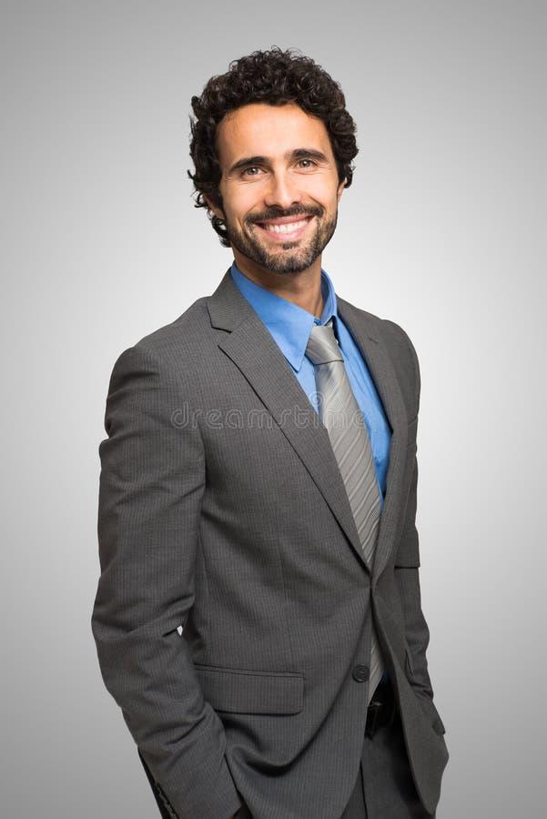 Retrato sonriente del hombre de negocios contra fondo gris fotos de archivo libres de regalías