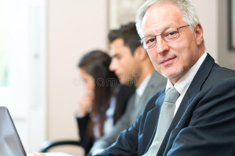 Retrato sonriente del hombre de negocios delante de su equipo imagen de archivo libre de regalías