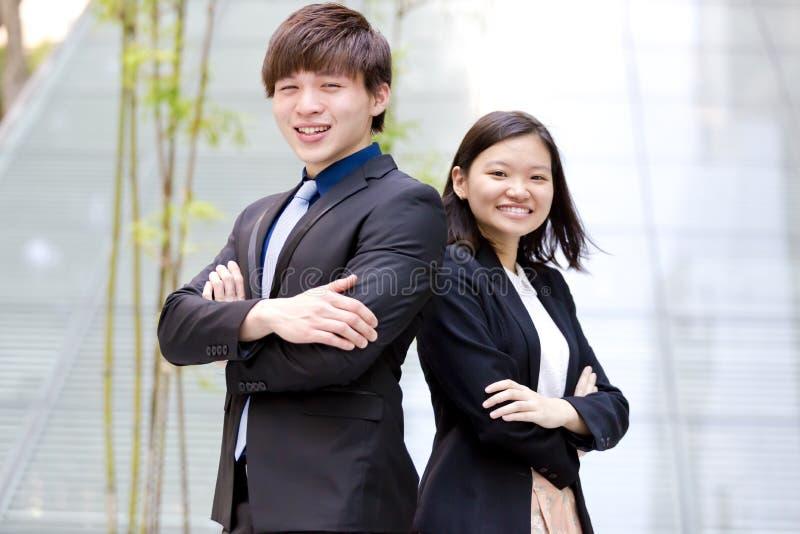 Retrato sonriente del varón asiático joven y del ejecutivo de operaciones de sexo femenino imagenes de archivo
