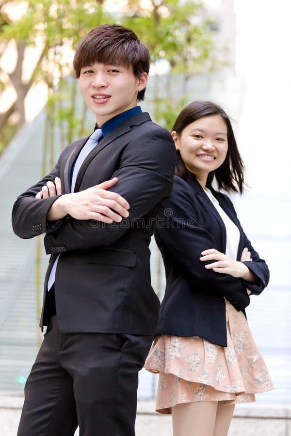 Retrato sonriente del varón asiático joven y del ejecutivo de operaciones de sexo femenino imagen de archivo