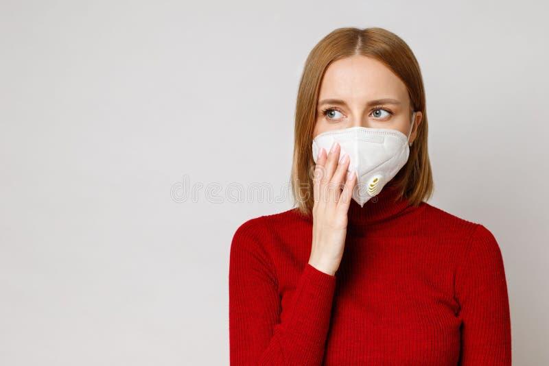 Retrato Studio de uma mulher usando uma máscara facial, fechar, isolado em fundo cinza Coronavírus, colo-19 fotografia de stock
