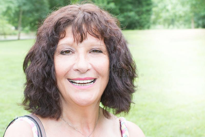 Retrato superior idoso de vista agradável de sorriso exterior da mulher fotos de stock royalty free