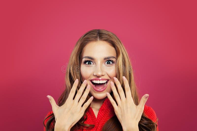 Retrato surpreendido feliz da menina Mulher entusiasmado com a boca aberta no fundo cor-de-rosa brilhante colorido Emoção positiv imagem de stock royalty free
