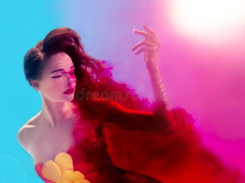 Retrato surrealista de la mujer atractiva joven con las burbujas de aire subacuáticas en agua colorida con tinta fotos de archivo libres de regalías