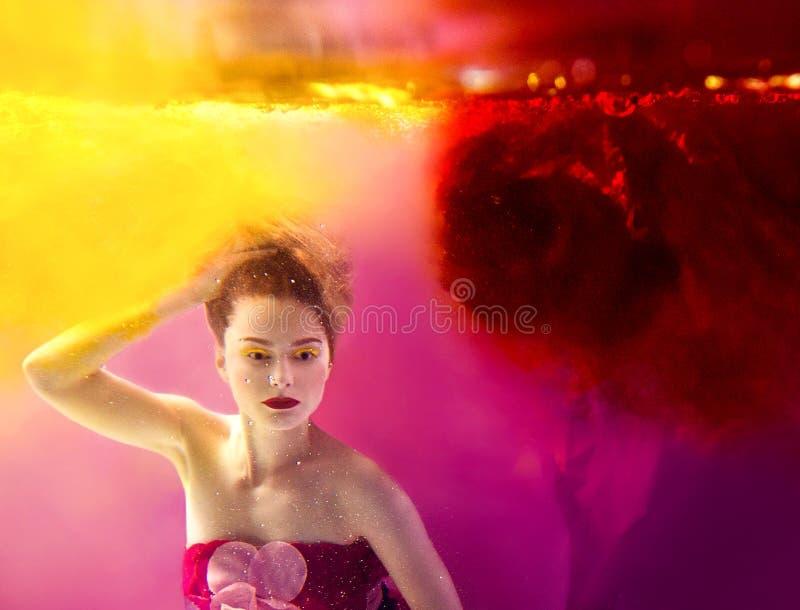 Retrato surrealista de la mujer atractiva joven subacuática en agua colorida fotografía de archivo