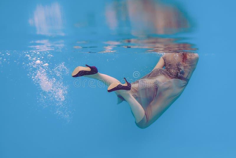 Retrato surrealista del arte hermoso asombroso de las piernas del ` s de la mujer en los zapatos violetas subacuáticos imagen de archivo