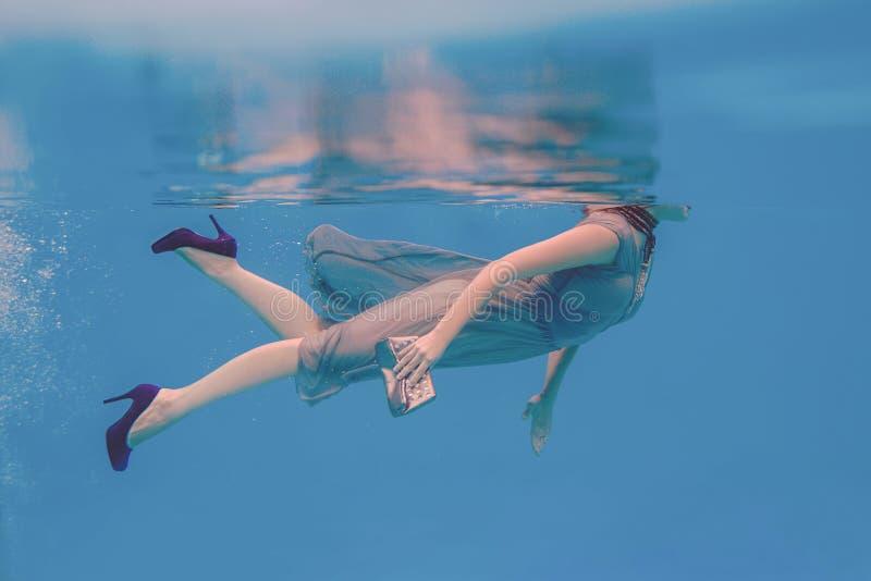 Retrato surrealista del arte del submarino de la mujer joven en la piscina fotografía de archivo